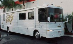 A Winnebago parked in the street.